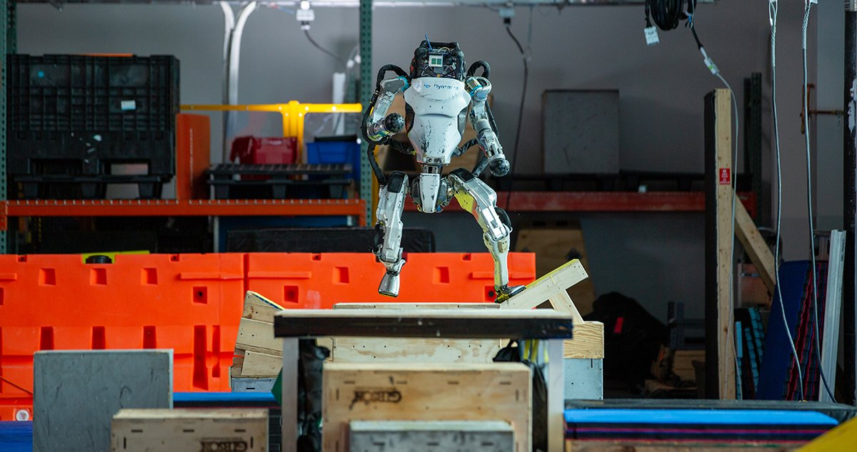 Atlas is mid-step running across a parkour course in the Boston Dynamics lab.